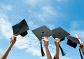 Graduates many hand holding graduation hats on background of blue sky Royalty Free Stock Images