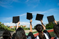 Graduates many hand holding graduation hats on background of blue sky Royalty Free Stock Image