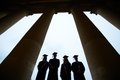 Graduates outlines of four between columns of university building Royalty Free Stock Images