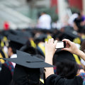 Graduates taking photos by cellphone during commencement Royalty Free Stock Photo
