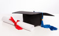 Graduation cap and diploma on white