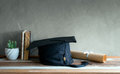 graduation cap, hat with degree paper on wood table graduation c Royalty Free Stock Photo