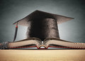 Graduation cap over the book with blackboard on background clipping path included Royalty Free Stock Photos