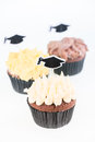 Graduation cupcakes with mortar board cake picks over white background Stock Photography