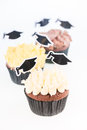 Graduation cupcakes with mortar board cake picks over white background Royalty Free Stock Photo