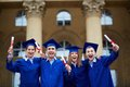 Graduation excitement group of smart students in gowns holding diplomas Royalty Free Stock Photography