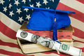 Graduation hat with cash diploma blue cap on old books on american flag Stock Photos