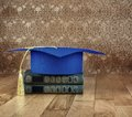 Graduation mortarboard on top of stack of books on a wooden table on background of vintage wall Royalty Free Stock Photography