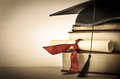 Graduation scroll and book stack a mortarboard tied with red ribbon on a of old battered with empty space to the left slightly Royalty Free Stock Photo