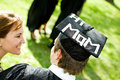 Graduation student with funny statement on hat extensive series of recent graduates after outside friends muti ethnic group Royalty Free Stock Photo