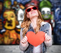 Graffiti urban lifestyle funky culture stylish teen girl wearing sunglasses and holding red paper heart modern love concept Royalty Free Stock Photography