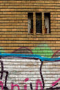 Grafitti on the bricks a wall in with a small window Royalty Free Stock Images