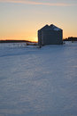 Grain bins winter sunset behind Royalty Free Stock Photo