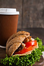 Grain croissant sandwich and a cardboard cup of coffee on a dark Royalty Free Stock Photo
