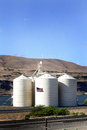 Grain elevator a large busy modern in eastern oregon on columbia river windmills on top of distant hills railroad tracks in Stock Photos