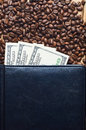Grains of coffee and money in a leather notebook. Coffee business. Royalty Free Stock Photo