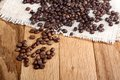 Grains of roasted coffee on linen napkin wooden table Stock Photography