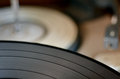 Gramophone vinyl record against old player in the background concept photo of retro music and sound Stock Photography