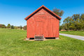 Granary a bright reddish wooden on the green grass with the blue sky in the background Stock Photo