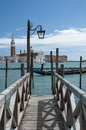 Grand canal jetty and gondolier with tourists on gondola Royalty Free Stock Photos