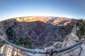 Grand canyon fisheye view of the at dawn taken from the south rim with a guardrail in the foreground Royalty Free Stock Photography