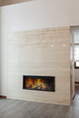 Grand design fireplace burning in marble wall Royalty Free Stock Photos