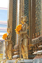 Grand palace bangkok thailand the golden statues with flowers at Royalty Free Stock Photography
