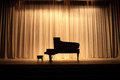 Grand piano at concert stage with brown curtain Stock Photo