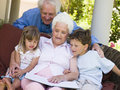 Grandchildren grandparents reading to Στοκ εικόνα με δικαίωμα ελεύθερης χρήσης