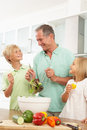 Grandchildren Helping Grandfather To Prepare Salad Stock Image