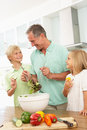 Grandchildren Helping Grandfather To Prepare Salad Royalty Free Stock Photos