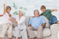 Grandchildren jumping on couch with their grandparents in the living room Royalty Free Stock Image