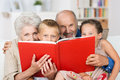 Grandchildren reading with their grandparents cute little boy and girl merry smiling eyes peering over the top of the book at the Stock Photo