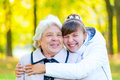 Granddaughter and grandmother embracing in autumn park Royalty Free Stock Images
