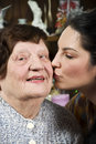 Granddaughter kissing her grandmother Royalty Free Stock Photography