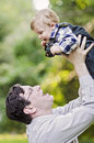 Grandfather and baby boy a happy held up by his Stock Images