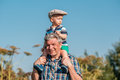 Grandfather carries grandson toddler boy on his shoulders Royalty Free Stock Photo
