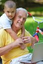 Grandfather and child using laptop happy elderly senior in park computer Royalty Free Stock Images