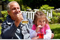 Grandfather drinks with his grandchild granddaughter outdoor Royalty Free Stock Photography