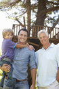 Grandfather, Father And Son Standing By Tree House Together