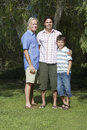 Grandfather, Father And Son Standing Under Tree