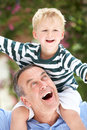Grandfather Giving Grandson Ride On Shoulders Royalty Free Stock Images