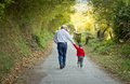 Grandfather and grandchild walking in nature path back view of a Stock Images