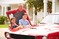 Grandfather with grandchildren cleaning restored classic car Royalty Free Stock Photography