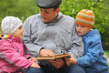 Grandfather with grandchildren reads book outdoor Royalty Free Stock Photography