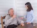 Grandfather and granddaughter communicating with his at table Royalty Free Stock Photo