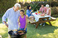 Grandfather and granddaughter preparing barbecue while family having meal Royalty Free Stock Photo