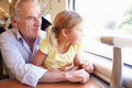 Grandfather and granddaughter relaxing on train journey looking off camera Royalty Free Stock Photos