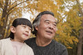 Grandfather and granddaughter smiling and looking away in park Royalty Free Stock Photo
