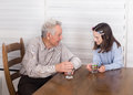 Grandfather and granddaughter talking smiling with his at table Stock Image